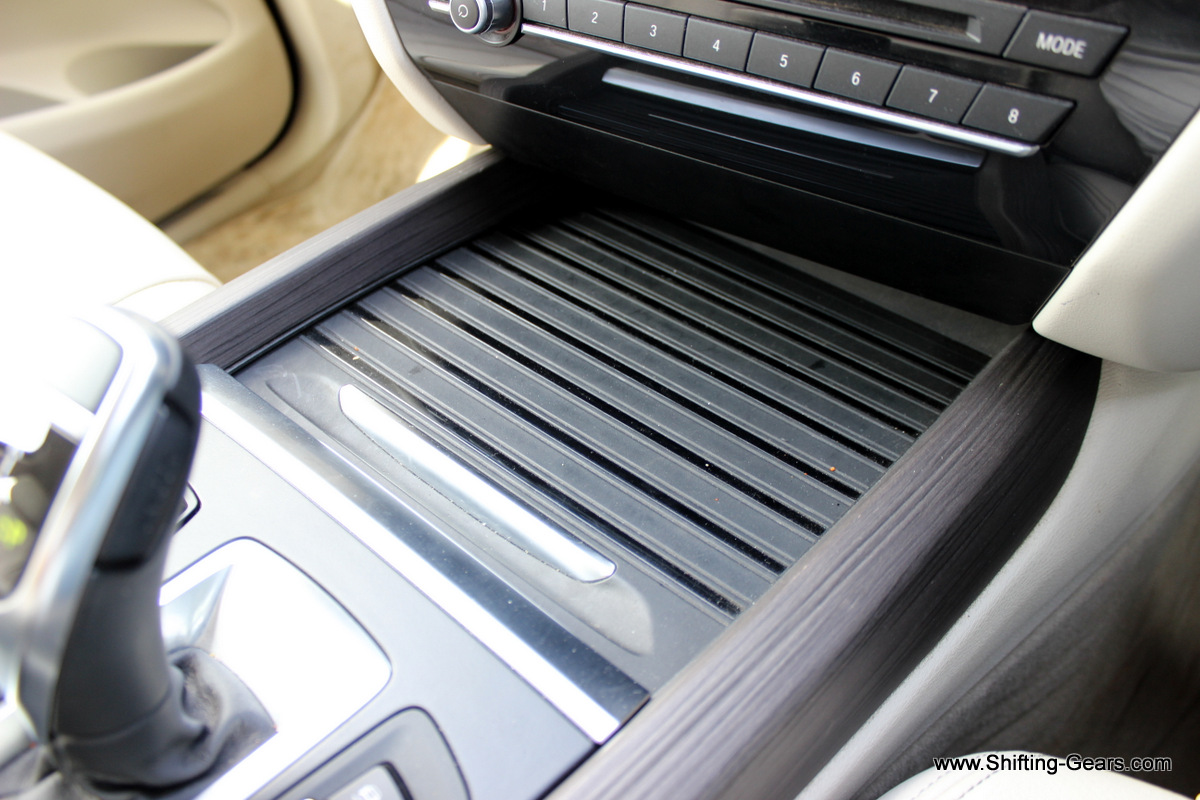 Storage bin below the centre console is neatly covered with a slider