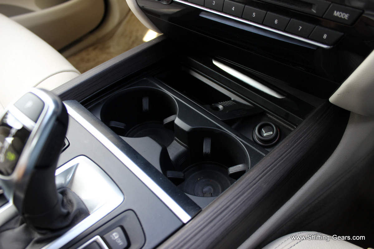 Two cup holders, a lighter and a cubby hole below the centre console