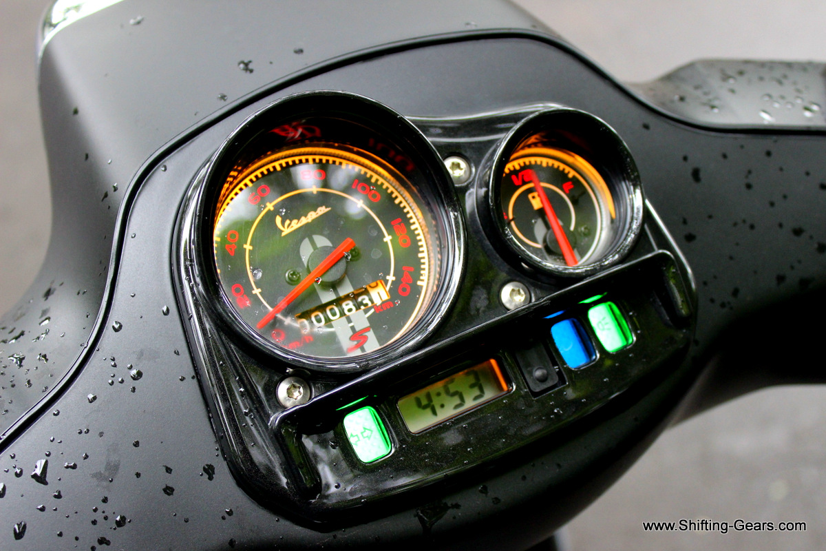 Instrument cluster gets gloss black plastic on top with a small wind deflector like design. Backlit in orange, this unit displays time, fuel gauge, speedometer and analogue odometer with a couple of tell-tale lights