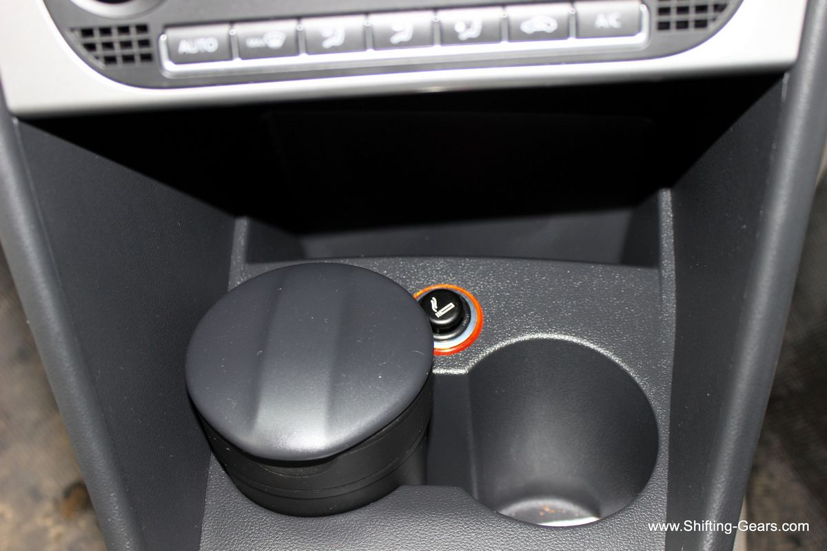 A storage bin below the AC control and two cup holders
