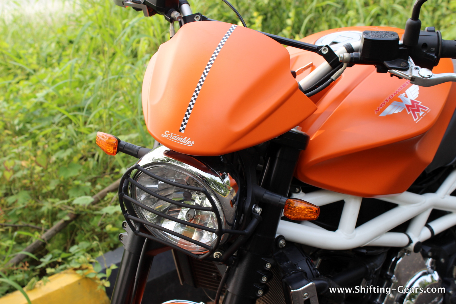 Round headlamp gets a metal guard to protect the lens and a small wind deflector on top with a chequered flag decal