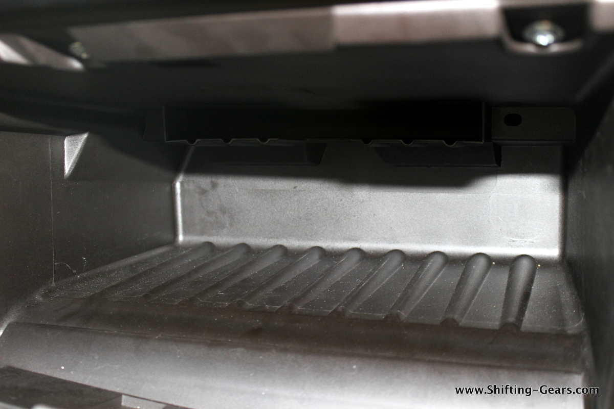 A small compartment on top, inside the glovebox to store your car manual